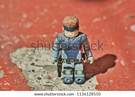A close up of a soldier figur showing bandana tactical vest and weapon holster with a shadow of the figure on the ground which is a brick step #1136128550