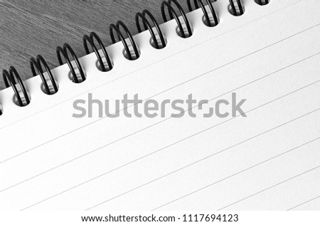 A close up of a spiral bound reporters notepad on a desk in black and white with copy space