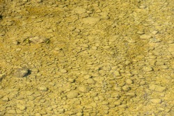 A close up of a stony riverbed under water background