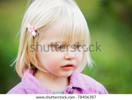 A close-up of a sweet little girl with beautiful features.  The little girl has blond hair, blue eyes and long eye-lashes.  She is looking to the side with a curious, relaxed look on her face.