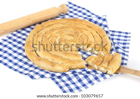a close up of a traditional Greek pie made of thin handmade pastry and  filled with goat cheese or feta cheese on a white and blue squared napkin, decorated with a wooden rolling pin - stock photo