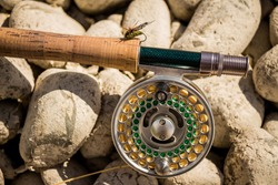 A close up of a trout fly rod, reel and line on rocks, with an artificial cicada fly attached to the cork