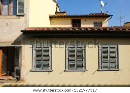A close up of a typical residential building in the center of Florence, Italy, with yellow walls and traditional green, wooden window shades. #1321977317