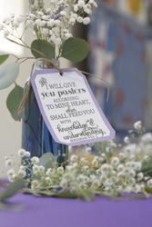 A close up of a vase filled and surrounded by baby breath flowers. On the vase is a sign with a Bible verse about pastors from the Book of Jeremiah.