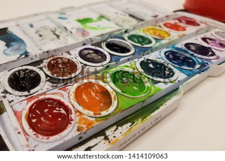A close up of a vibrant, messy watercolor paint palette on white paper.