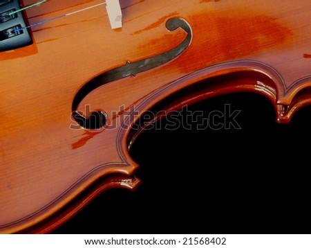 A close up of a violin including f hole.