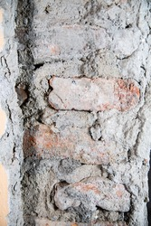 A close-up of a wall with stripped plaster and uncovered brickwork. Renovation of a house, a flat.