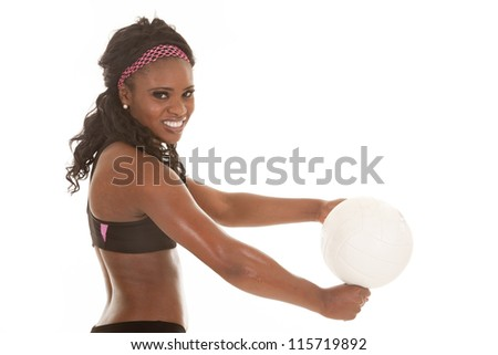 A close up of a woman getting ready to hit a volleyball with a smile on her face.