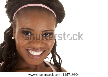 A close up of a woman's face with a pink head band and a smile.