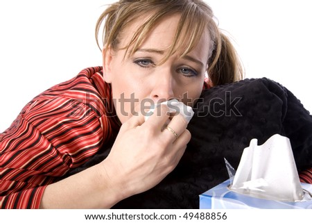 A close up of a woman who has a cold and doesn't feel very good holding her blanket and cleaning off her nose.