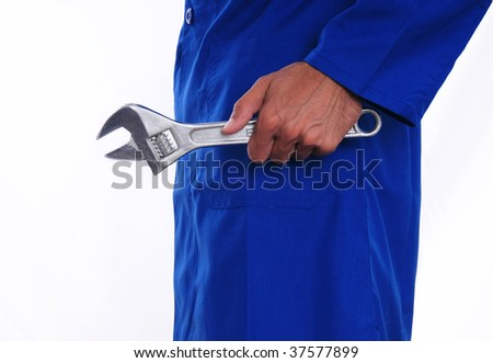 A close up of a worker holding a wrench by his side. The man is wearing a blue jumpsuit.