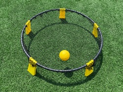 A close up of a yellow and black spike ball game set up on a green turf field with the yellow ball on the net.