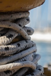 A close up of a yellow mooring  rope - rope binding  in a port. With some blurry background of boats.