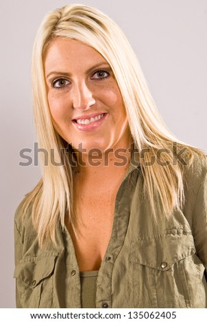 A close up of a young Caucasian blonde female facing left of camera with her head turned to the camera and smiling.