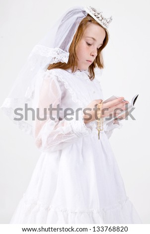A close-up of a young girl smiling in her First Communion Dress and Veil, reading a bible while holding her rosary beads with a cross