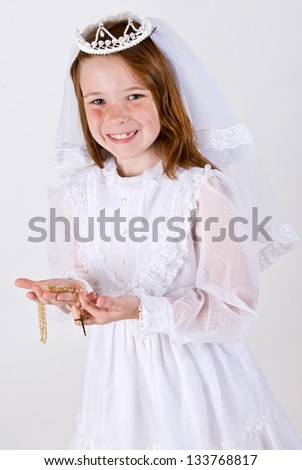 A close-up of a young girl smiling in her First Communion Dress and Veil while holding her rosary beads with a cross..