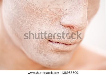 A close-up of a young male model\'s face with foundation applied to it.