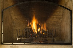A close up of aflame wood fireplace for warm and cold weather