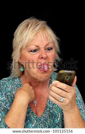 A close-up of an attractive, older blonde woman who is angered by something on her cellular phone and sticking her tongue out at it.