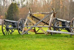 A close up of an old grey slightly rusty WWI wheel cannon replica with a big barrel standing on a field next to a wooden barrier or protection seen on a sunny autumn day on a Polish countryside