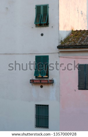 A close up of an old residential building in Lucca, Italy, with white and pink colored walls and green window shades. #1357000928