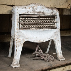 A close up of an old retro electric fire. It is dusty and the electric cable is frayed. It has three elements