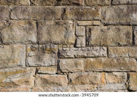 a close up of an old stone wall made from huge blocks of sandstone