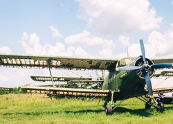 A close-up of an old wrecked passenger plane that has been decommissioned and stands for tourists. The fuselage shows traces of rust and chips. Parts of the metal structure are visible on the wings