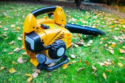 A close-up of an orange cordless, electric leaf blower lying on a grass. Autumn, fall gardening works in a backyard, on a lawn. Garden works.