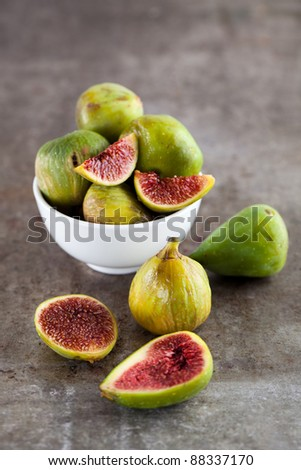 A close-up of assorted fresh figs on a rustic metal surface.