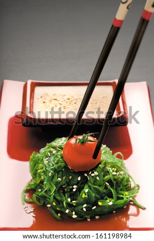 A close-up of chopsticks holding a red-ripe tomato on chuka salad along with gomadare sauce in the background.