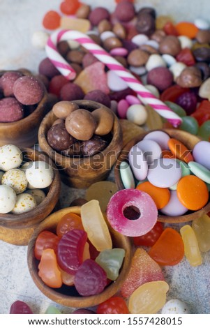 A close up of colorful bright assorted sweets and candy for kids party on white table, assortment of many candies  #1557428015