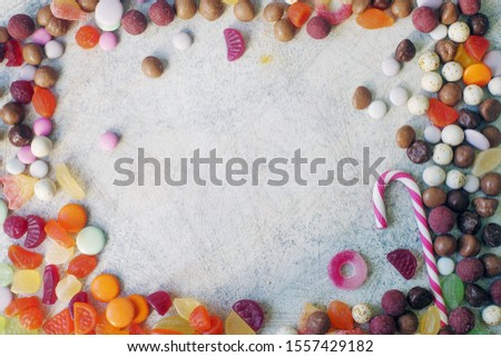 A close up of colorful bright assorted sweets and candy for kids party on white table, assortment of many candies with copy space #1557429182