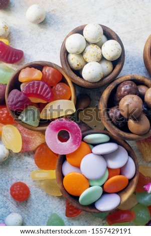 A close up of colorful bright assorted sweets and candy for kids party on white table, assortment of many candies  #1557429191