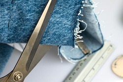A close up of cutting denim jeans material with scissors, a ruler and a tailor's chalk in the background.