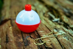 A close up of fishing a boober and hooks laying on top of a piece of wood- a red and white fishing bobber with some gold colored hooks in front of it- fishing gear, or tackle- floater and hooks