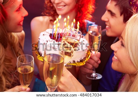 A close up of four clinking glasses against the girl holding her birthday cake among her friends