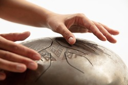 A close up of hands playing the hank drum on white studio background. Concept of hobby, professional occupation, music, traditions, festival. Copyspace for your ad. Ethnic instrument.