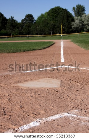 A close-up of home plate and the batters boxes at a baseball field.