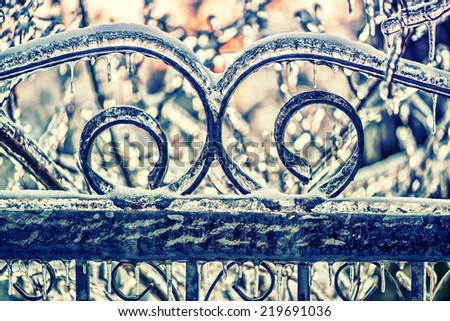 A close up of part of an ornamental wrought iron gate with curve patterns covered in a thick layer of ice and icicles after an ice storm.  Filtered for a retro, vintage look.