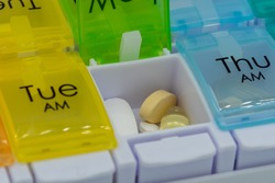 A close up of pills inside a pill box or medication box used for counting out medication for the week