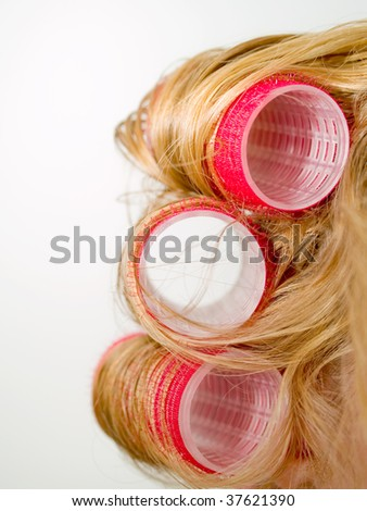 A close-up of red curlers in blond hair