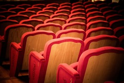 A close up of row of red empty theatre chairs shot from the back with dark vignette