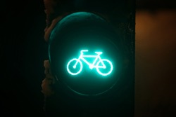 A close up of scoreboad showing green light for bicycles during snowfall.