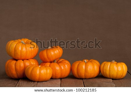 A Close Up of Several Small Pumpkins Lined up in a Row on Rustic Old Wooden Boards against Medium Brown Background with Copy Space