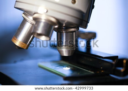 A close up of specimen stage, lenses, and slide of a laboratory microscope ready for examination.