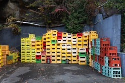 A close up of stacks of plastic multicolor crates containing beer and soft drink bottles in Japan. Old beverage plastic bottle,