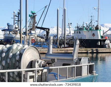 A close up of the back of a fishing boat with a net reel in the harbor with other boats in the background
