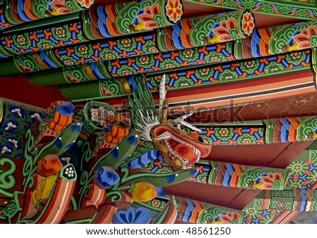 A close-up of the decorative rafters and eaves of a Korean temple.