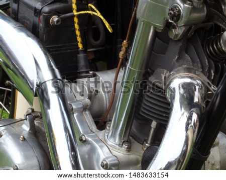 a close up of the engine and frame on an vintage motorbike with black cylinders and chrome pipes #1483633154